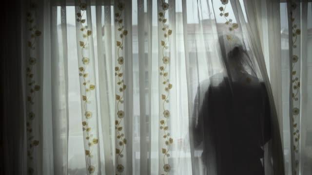 spårning skott av en ung mans silhuett tittar på tomma gator från hans fönster - sentimentalitet bildbanksvideor och videomaterial från bakom kulisserna