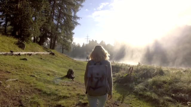 Tracking shot of a young woman walking by the lake at sunrise video