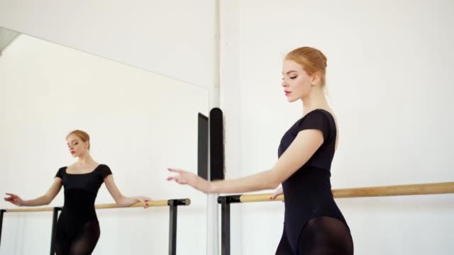 vidéos et rushes de tir de suivi de la belle ballerine dans le justaucorps noir pratiquant à barre dans le studio de danse de ballet avec les murs blancs et le miroir - justaucorps