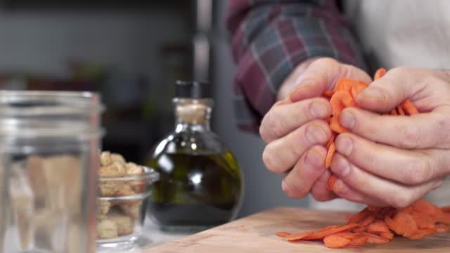 spårning skott av kocken ösa upp färska skivade morötter och dumpning dem i mason jar - konserveringsburk bildbanksvideor och videomaterial från bakom kulisserna