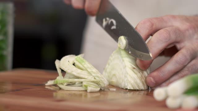 stockvideo's en b-roll-footage met tracking shot van chef-kok moten verse venkel op snijplank - venkel