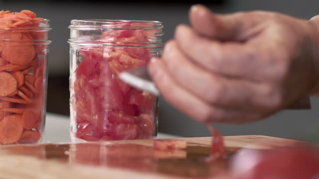 spårning skott av kocken använda kniv för att plocka upp skivad tomat och lagra i mason jar - konserveringsburk bildbanksvideor och videomaterial från bakom kulisserna