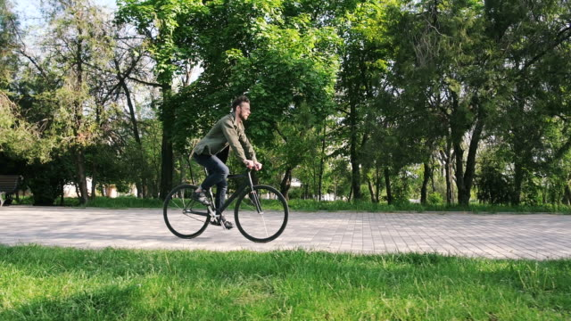 stockvideo's en b-roll-footage met tracking shot van hipster man rijden vaste gear fiets in park, slow-motion - ongewerveld dier