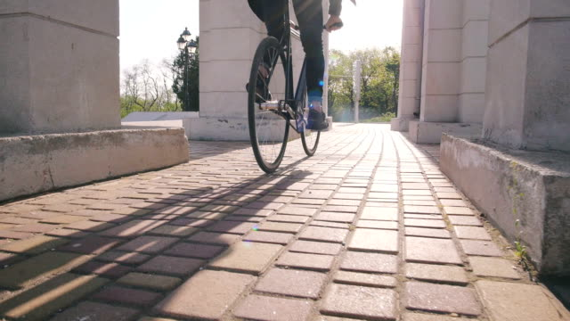 Tracking shot of hipster man riding fixed gear bicycle in park, slow motion video