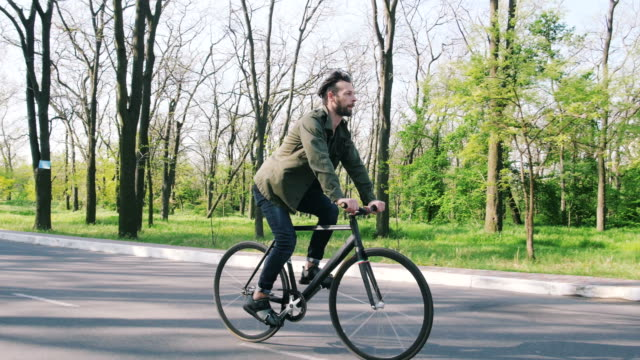 stockvideo's en b-roll-footage met tracking shot van hipster man rijden vaste gear fiets in park - ongewerveld dier