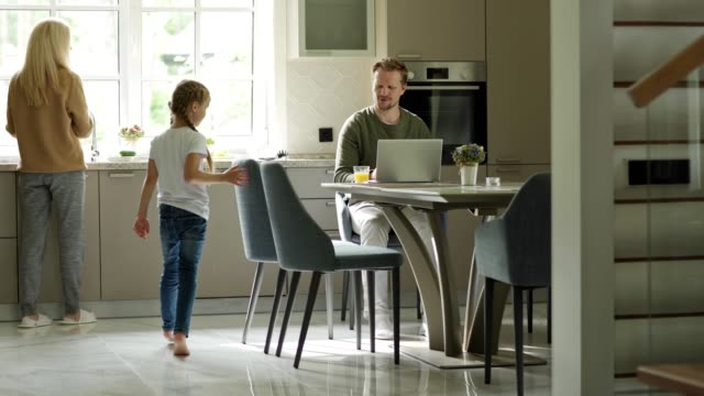 Tracking shot of man working on laptop sitting at table in domestic kitchen. Little daughter running downstairs to him, caring mother giving her glass of orange juice. Family gathering at table – film