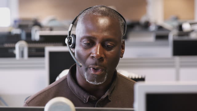 Tracking shot of mature businessman wearing headset working in call center talking to client - shot in slow motion
