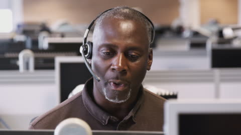 vídeos de stock e filmes b-roll de tracking shot of mature businessman wearing headset working in call center talking to client - shot in slow motion - cuidado