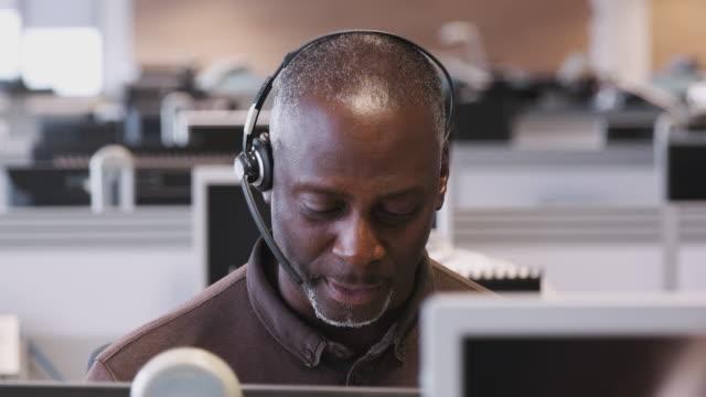 vidéos et rushes de tir de suivi de l'homme d'affaires mûr utilisant le casque travaillant dans le centre d'appel parlant au client - tiré au ralenti - opérateur téléphonique