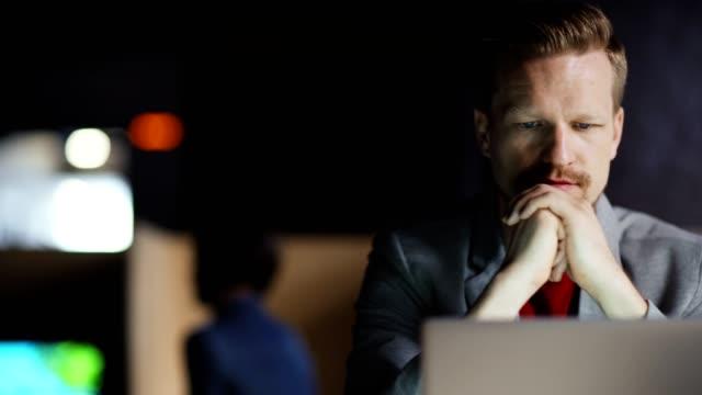 tracking-aufnahme von geschäftsmann mittleren alters sitzt am büroschreibtisch in der nacht, lesen dokument auf laptop-bildschirm mit seiner hand auf dem kinn und denken - introspektion stock-videos und b-roll-filmmaterial