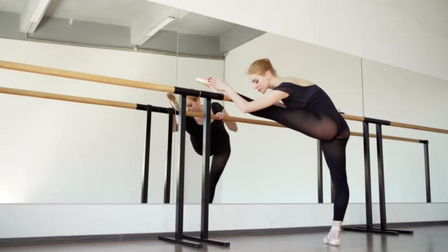 tracking shot of professional young ballerina in black leotard and pointe shoes stretching at barre in ballet dance studio - studio tańca filmów i materiałów b-roll