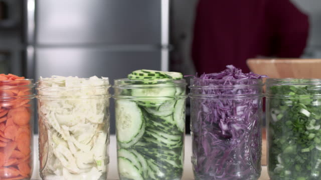 spårning skott av sallad ingredienser i mason jars medan kocken kockar i bakgrunden - konserveringsburk bildbanksvideor och videomaterial från bakom kulisserna