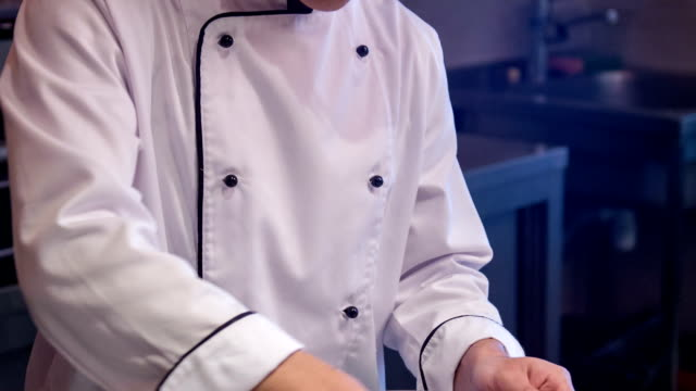 Tracking shot of smiling Asian chef in white uniform video