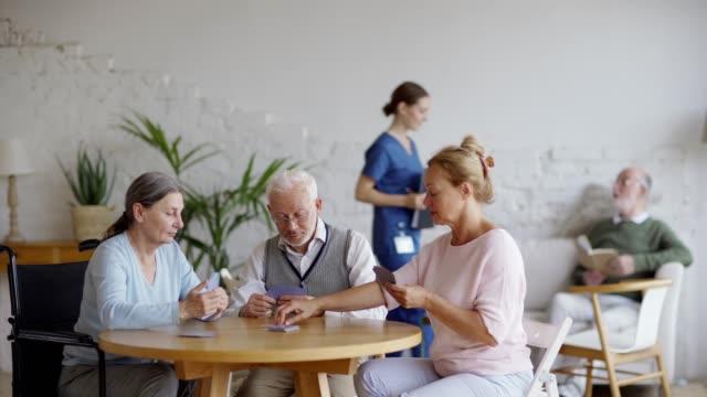 支援生活の家でテーブルに座ってトランプゲームをプレイする3人の先輩の友人の追跡ショット。バックグラウンドでソファの上で本を読んで男性の高齢患者に話すクリップボアドを持つ看護 - 介護点の映像素材/bロール