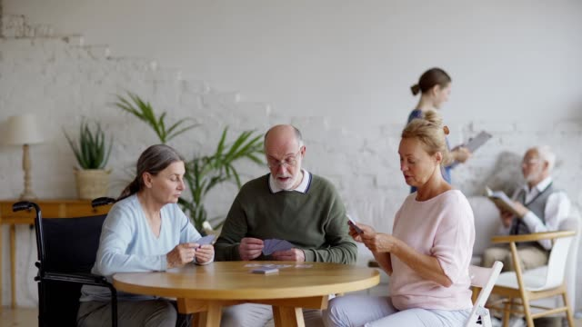 Tracking shot of three senior people playing cards sitting at table in nursing home. Young nurse talking to male aged patient reading book on sofa in background