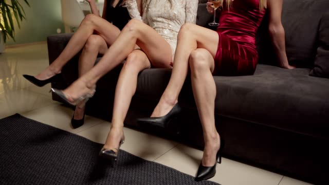 Tracking shot of three unrecognizable young women with beautiful legs sitting cross-legged on sofa holding wine glasses at house party. Elegant women in high heels shoes recrossing their slim legs