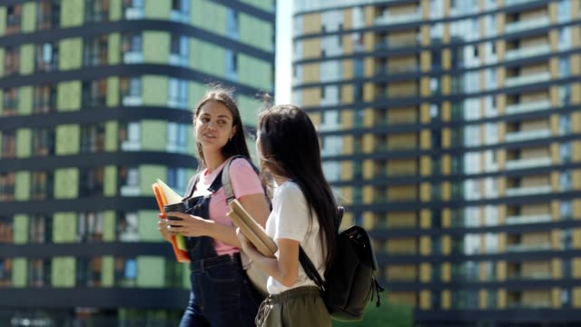 tracking shot of two diverse female college students, asian and caucasian, with backpacks, textbooks and binders talking while walking down street after classes - two students together asian video stock e b–roll