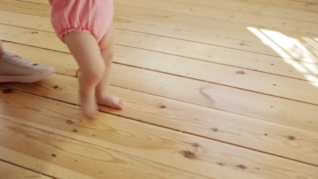 Tracking shot of unrecognizable caring mother supporting her adorable baby daughter learning to walk and making her first steps on hardwood floor at home Tracking shot of unrecognizable caring mother supporting her adorable baby daughter learning to walk and making her first steps on hardwood floor at home first occurrence stock videos & royalty-free footage