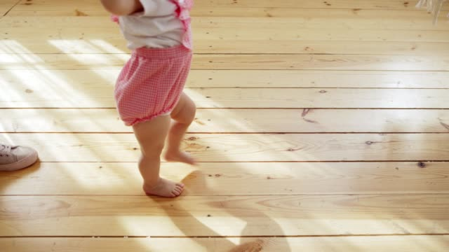 Tracking shot of unrecognizable mother helping her lovely baby girl to make her first steps on hardwood floor