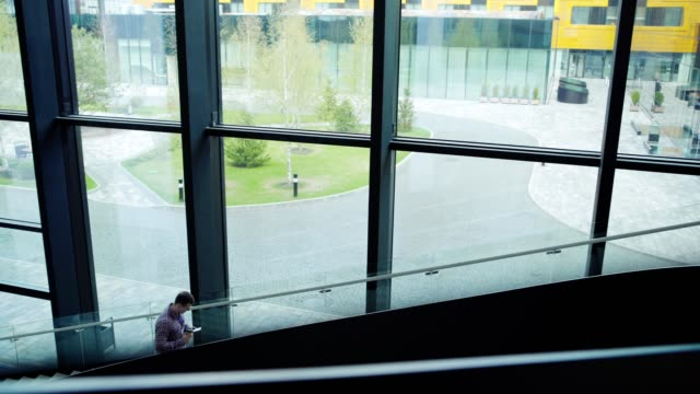 Tracking shot of young employee walking upstairs in office building, texting on cell phone and drinking coffee