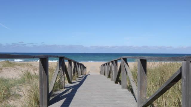 tracking shot on walkway to the beach
