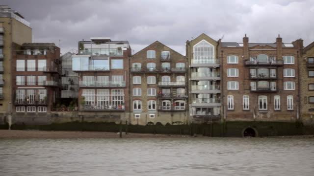 tracking shot passerar hus och strukturer på themsen bank i london - kameraåkning på räls bildbanksvideor och videomaterial från bakom kulisserna