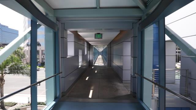 tracking shot through modern hospital hallway/skyway - carrellata video stock e b–roll