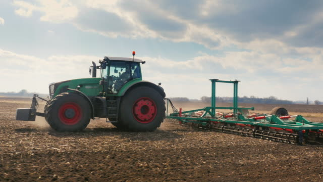 Tracking shot: tractor Plows the land in the field. Spring field works. Beautiful sunny day in good weather. 3-axis stabilized video video