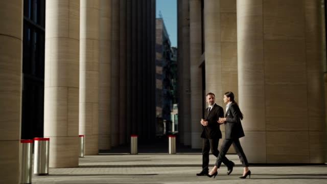 spårning sida visa skott av två affärsfolk, medelålders man och ung kvinna i svart formella kostymer med takeaway kaffekoppar lämnar kontorsbyggnad och gå ner på gatan tillsammans pratar - kostym sida bildbanksvideor och videomaterial från bakom kulisserna