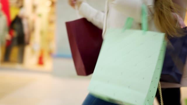 stockvideo's en b-roll-footage met volgen zijaanzicht shot van twee onherkenbaar shopaholic vrouwen met boodschappentassen lopen langs mall haasten om aankopen te doen op de verkoop dag - black friday shop