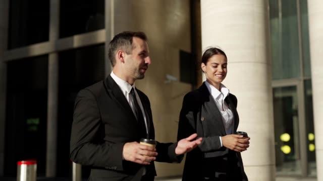 spårning slow motion skott av två företagare i formella kostymer, medelålders man och ung kvinna gå ner gatan med takeaway kaffekoppar och talande vänlig - kostym sida bildbanksvideor och videomaterial från bakom kulisserna