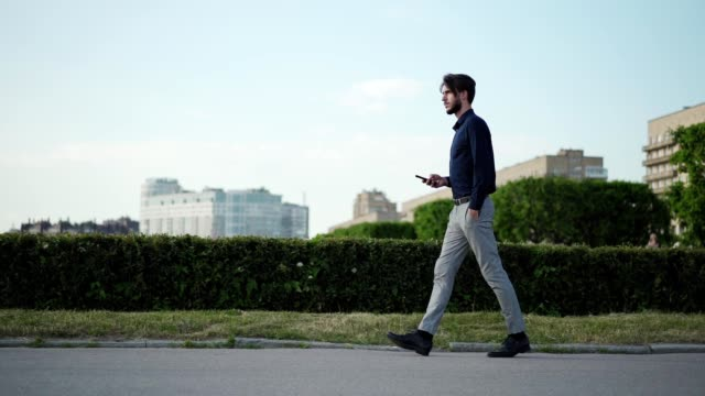 tracking slow motion shot of young businessman text messaging on cell phone while walking down street confidently with hand in pocket - carrellata video stock e b–roll