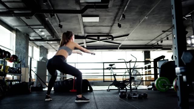 vídeos de stock e filmes b-roll de tracking wide shot back view of fit young woman in crop top and leggings doing squats to warm up during cross training in gym - agachar se