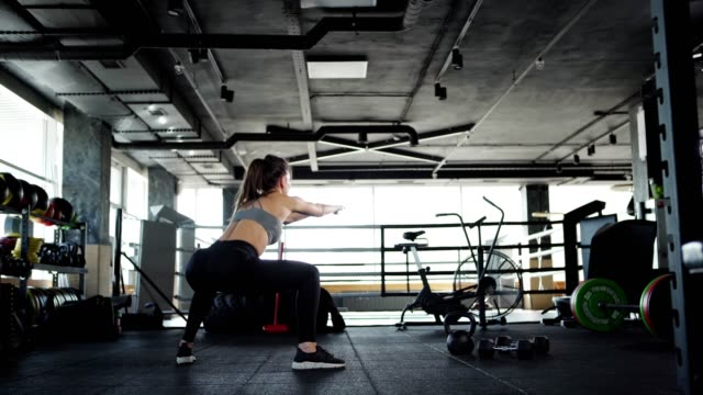 vídeos de stock e filmes b-roll de tracking wide shot three quarter angle back view of athletic young woman in crop top and leggings doing squats to warm up in gym - agachar se
