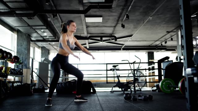 vídeos de stock e filmes b-roll de tracking wide shot three quarter angle of fit young woman doing squats to warm up during cross training in gym - agachar se