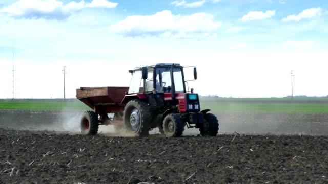 tractor and fertilizer spreader on the field - fertilizzante video stock e b–roll