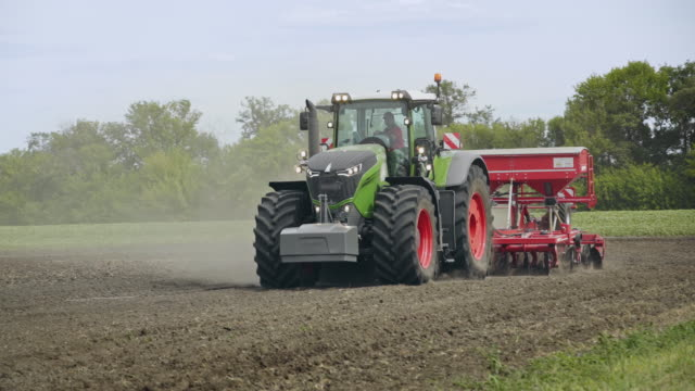 Tractor and field. Farm tractor with trailer seeder sowing agricultural field video