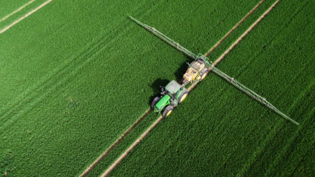 AERIAL: Tractor Applying Fertilizer to Corn Field video