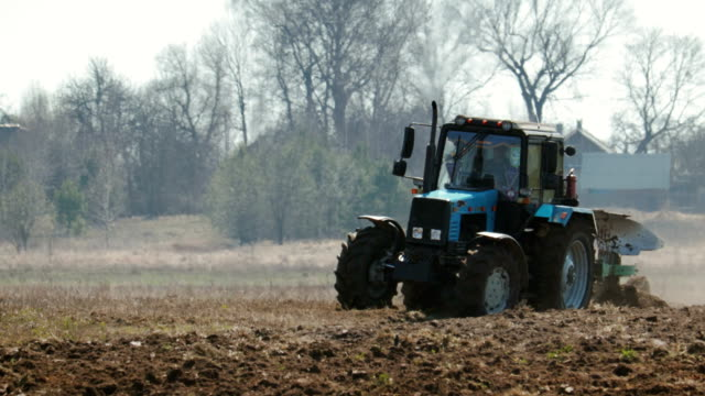 tractor blue colour with big black wheels and a powerful grouser, heavy plows dark fertile soil. the warmth from the ground and the machine motor distorts the image - białoruś filmów i materiałów b-roll