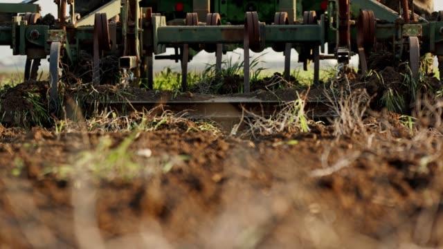 vídeos de stock e filmes b-roll de tractor cultivating a green field in slow motion. - terra cultivada