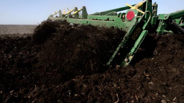 vídeos de stock e filmes b-roll de tractor cultivating land in extreme close-up - terra cultivada