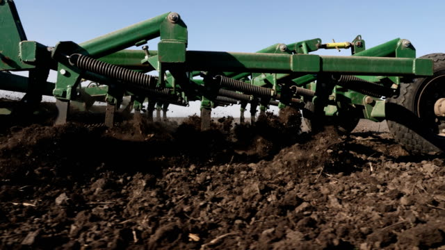 Tractor cultivating land in extreme close-up Tractor cultivating land in extreme close-up. Tractor disc ground. Rural locality. Steadicam shot The camera moves with the cultivator. Tractor handles field. Disking. The land is ready for planting. plow stock videos & royalty-free footage