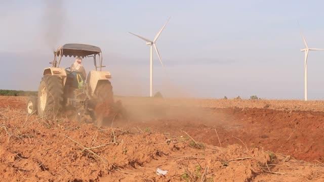 mavi gökyüzü ile kara yetiştirilmesi traktör. - start stok videoları ve detay görüntü çekimi