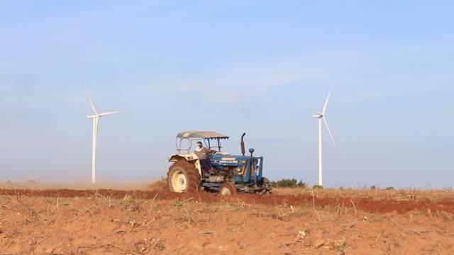 traktör yetiştirilmesi arazi gökyüzü ile. - start stok videoları ve detay görüntü çekimi