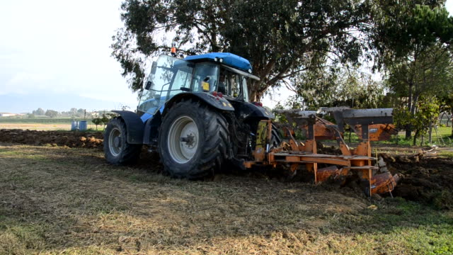 Tractor digging furrows in the ground video
