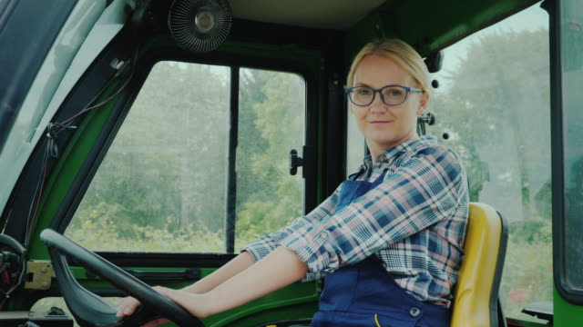 Tractor driver woman portrait. Smiling, looking at the camera video