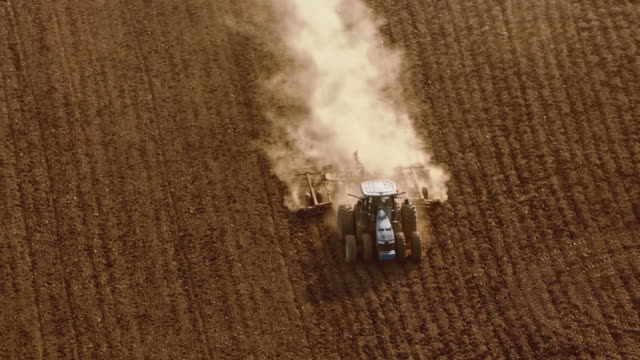aerial tractor driving across a vast field in sunshine - trattore video stock e b–roll