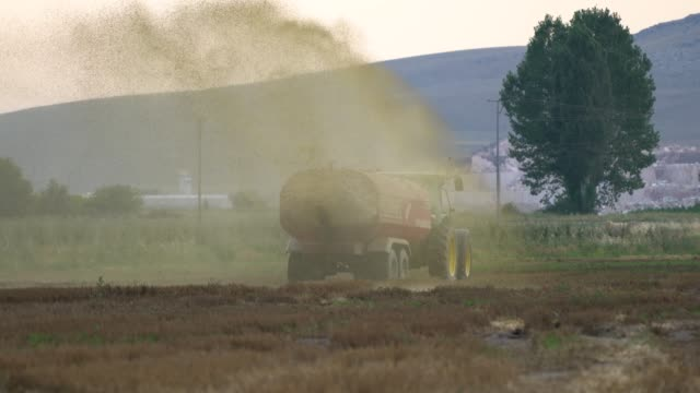 tractor fertilization in agricultural field - fertilizzante video stock e b–roll