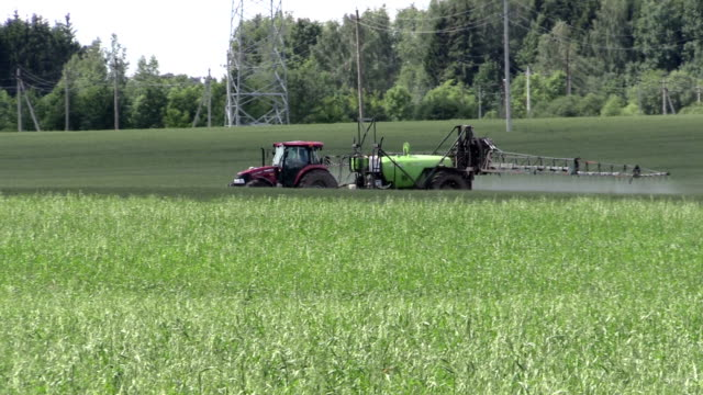 tractor fertilize crop field at herbicides, pesticides. Panning video