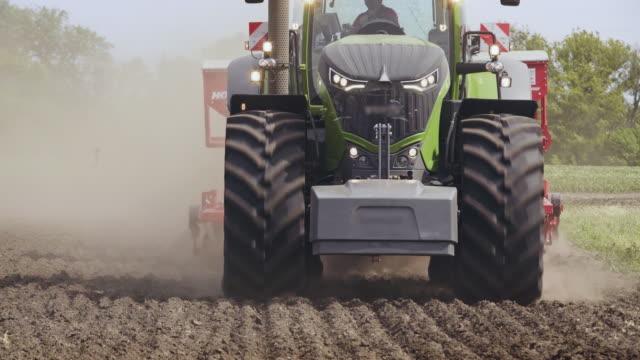 vídeos de stock e filmes b-roll de tractor field. agricultural tractor driving on arable field. agricultural field - trator